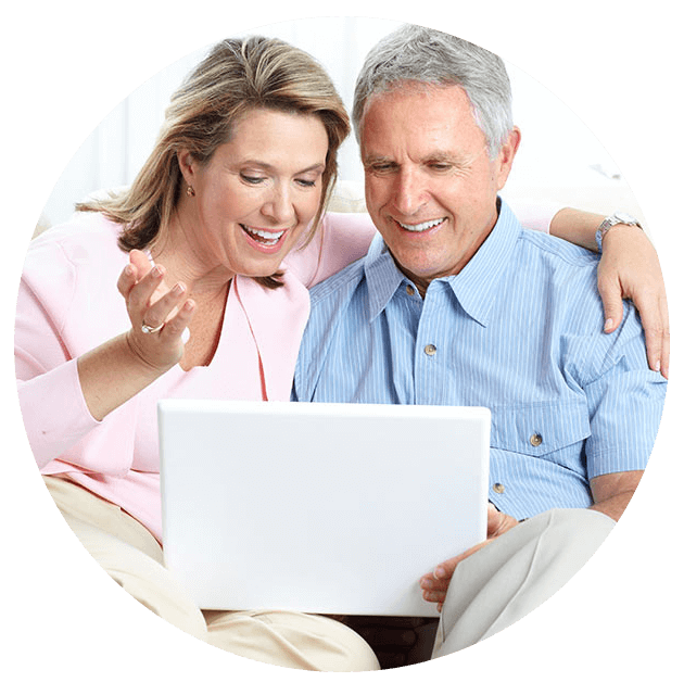 Man and woman smiling while looking at a laptop computer.