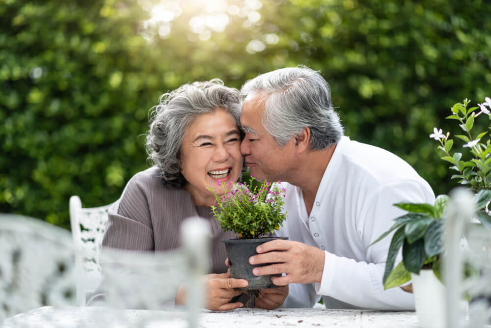 Elderly couple with gray hair holding a plant outdoors