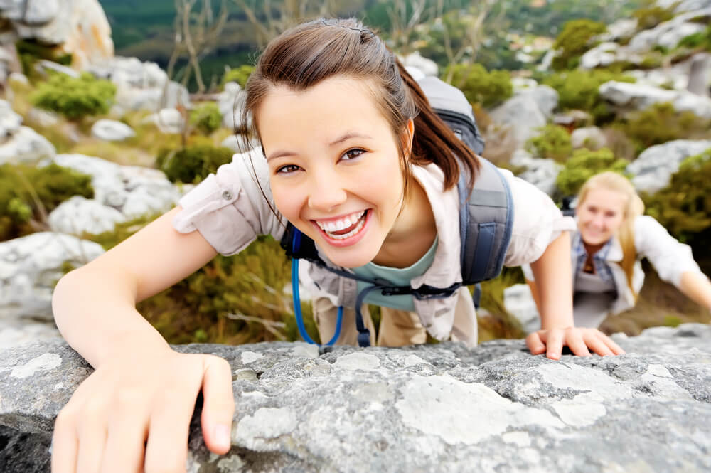 Young woman rock climbing and smiling
