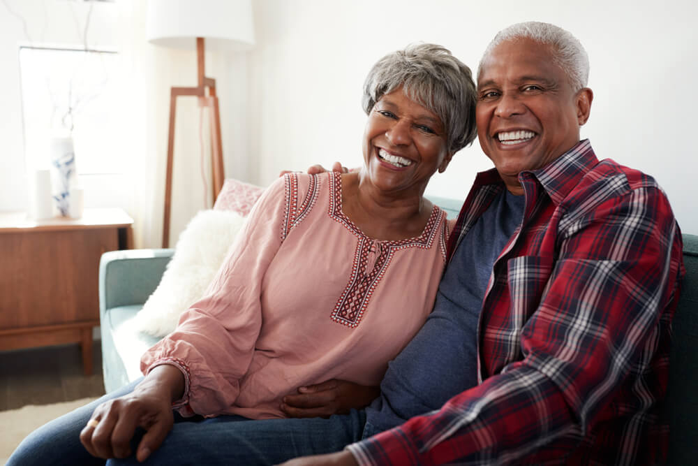 Couple in their 60s sitting on couch together and smiling