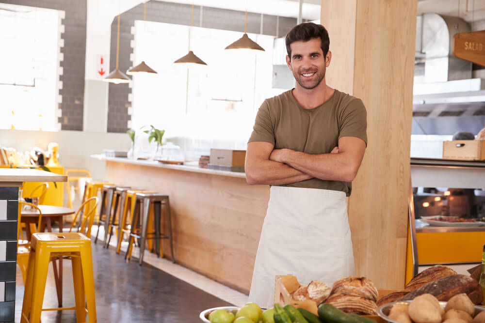 Man in his 30s wearing an apron in his cafe