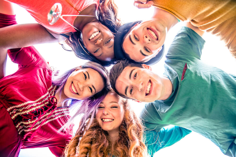 Teenagers in bright colors in a circle and smiling