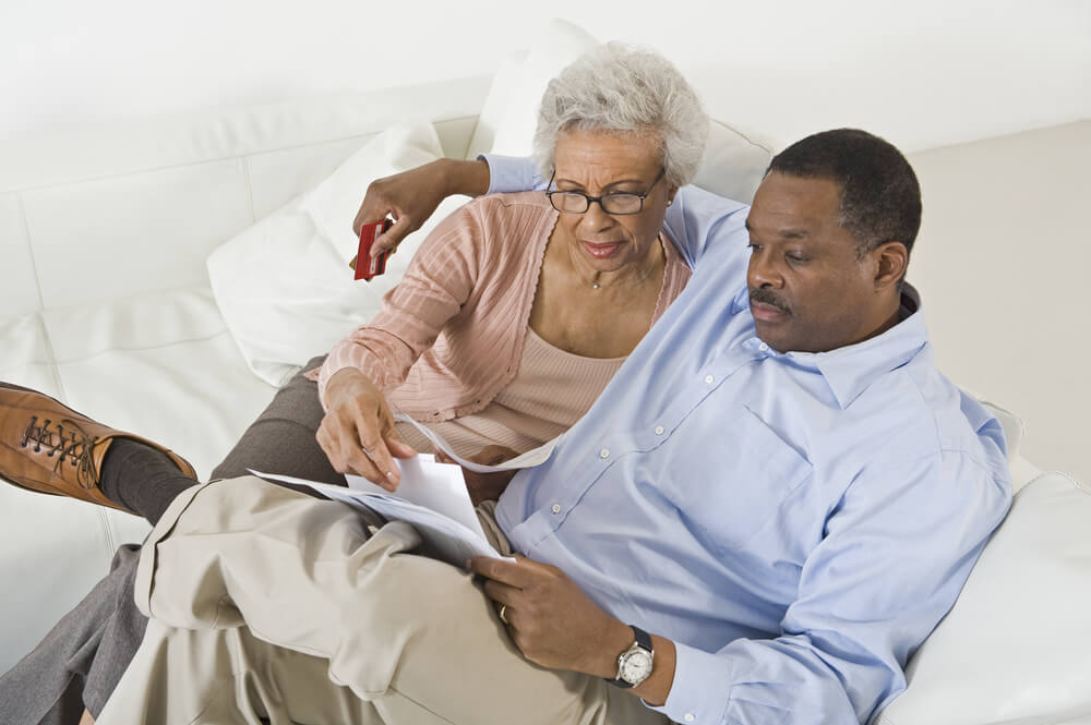 Mother and son reviewing paperwork on a white couch