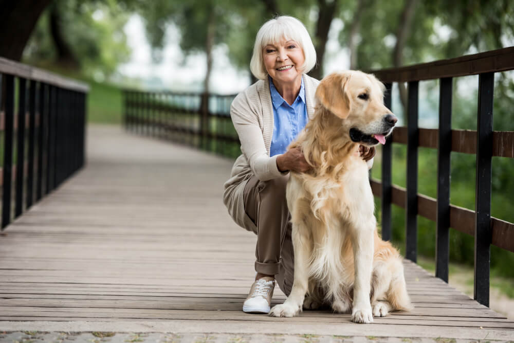 Senior woman with dog on a wooden bridge walkway