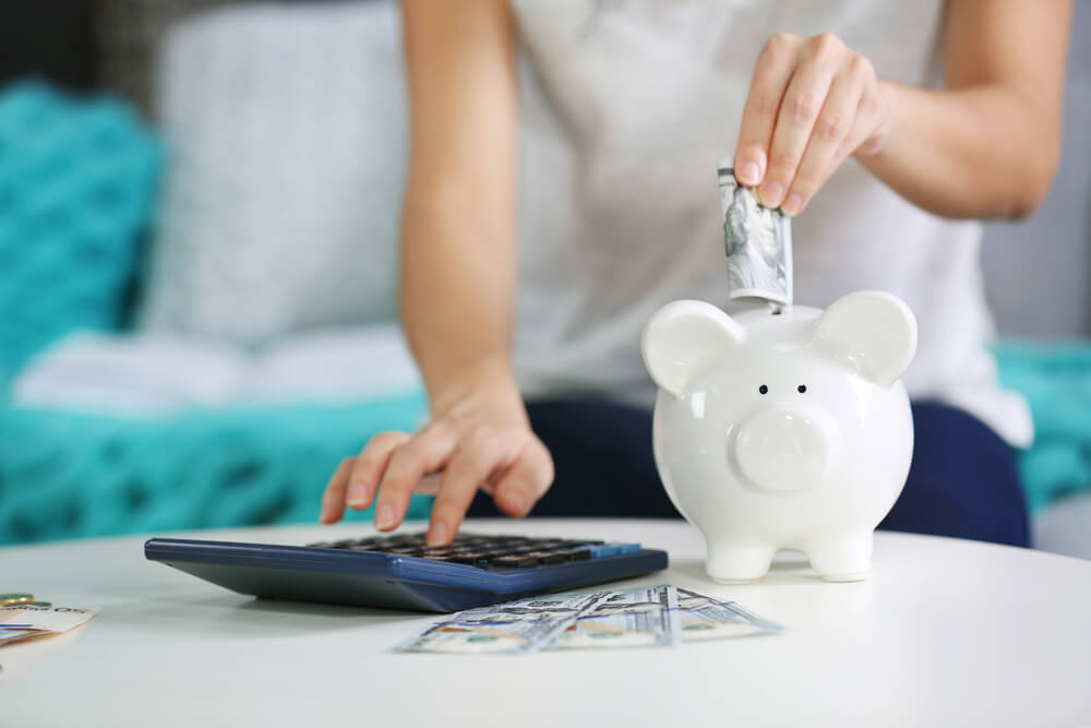 Woman putting money in a white piggy bank