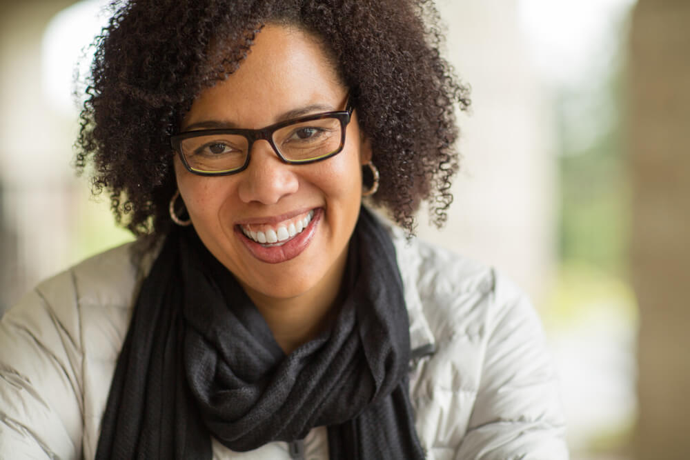 Middle-aged woman in glasses and scarf, smiling